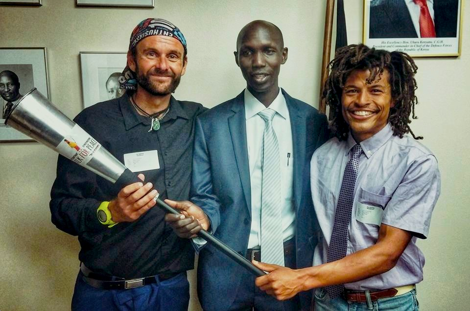 Pat Sweeney (left) and Alex Ramsey (right) present Wilson Kipsang with the 'torch for humanity' at Kenya's Embassy to the United Nations, New York, 2 November 2015