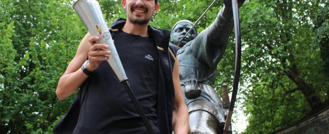 Adam Holland holds the Kenya Peace Torch beside the Robin Hood statue at Nottingham Castle, having won the 2016 Robin Hood Marathon. He is set to be the only athlete completing the 1,000km Kenya Peace Torch Relay.